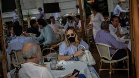A client wearing a protective face mask has lunch in a bar terrace in Madrid, Spain, Monday, May 25, 2020.