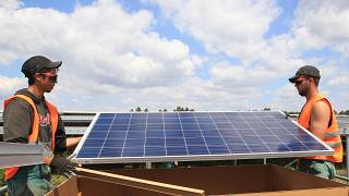 Workers install solar panels at the Constantine photovoltaic power station in Cestas, near Bordeaux, southwestern France, Friday, May 22, 2015.