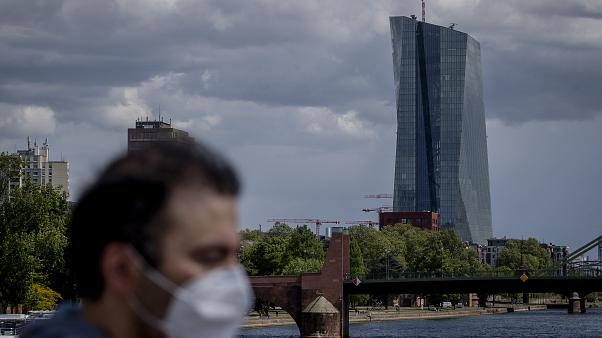 Man with mask passing by ECB Building