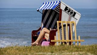 A woman is sunbathing on a beach chair by the sea in Norderney, Lower Saxony, Germany Tuesday May 26, 2020