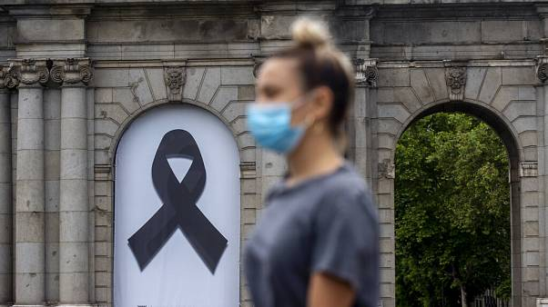 A woman wearing a face mask to protect against coronavirus, walks in front of a black ribbon for the victims of COVID-19, displayed at Puerta de Alcala square in downtown Madr