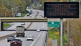 "A digital PennDOT sign reminds drivers to ""Continue Social Distancing"" as cars and trucks travel on U.S. Route 22."
