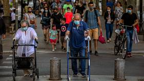 People walk on a street in Barcelona on Monday, May 25, 2020.