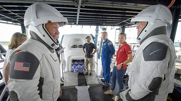 In this Aug. 13, 2019 file photo, NASA astronauts Doug Hurley, left, and Bob Behnken work with teams from NASA and SpaceX to rehearse crew extraction from SpaceX's Crew Dragon