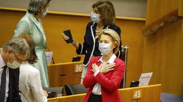 European Commission President Ursula von der Leyen, right, gestures hello to an MEP prior to addressing the European Parliament plenary in Brussels, Wednesday, May 27, 2020.