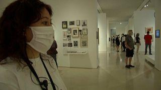 Una joven con mascarilla observa una obra de arte en un museo de Málaga