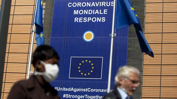 A woman wearing mouth mask, to prevent against the spread of the coronavirus, COVID-19, walks past EU headquarters in Brussels, Thursday, May 7, 2020.