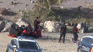 Policías nacionales reciben a un grupo de migrantes en una playa de Gran Canaria