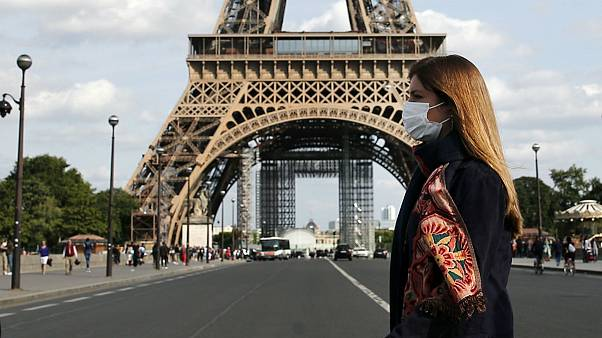 A woman wearing protective face mask walks next to the Eiffel Tower in Paris