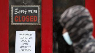 شخص يمشي امام متجر مغلق في الولايات المتحدة بسبب إجراءات الإغلاق جراء كورونا