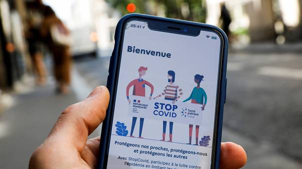 A man holds a mobile phone displaying a screenshot of the tracking application StopCovid developed by the French government.