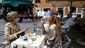 A woman sips coffee under her face sheild at a cafe with outdoor tables in Rome Monday, May 18, 2020.