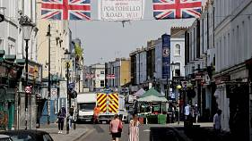 People walk along Portobello Road Market in London, Wednesday, May 27, 2020.