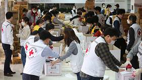 Red Cross workers prepare emergency relief kits packed with basic necessities for delivery  at a facility of the Korean National Red Cross in Seoul, March 27, 2020