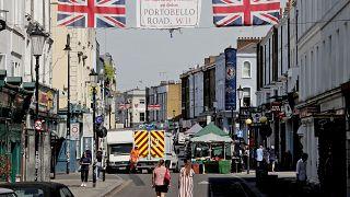 People walk along Portobello Road Market in London, Wednesday, May 27, 2020.