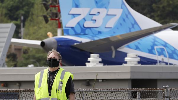 A masked worker walks in view of a 737 jet at a Boeing airplane manufacturing plant