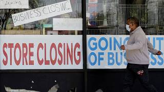 A man looks at signs of a closed store due to COVID-19 in Niles, Ill., Thursday, May 21, 2020.