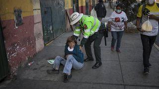 Un policía ayuda a una mujer tendida en una calle de Lima, Perú
