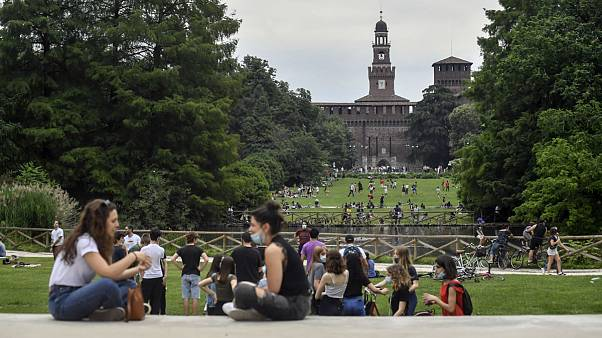 People enjoy sitting in a park in central Milan, northern Italy