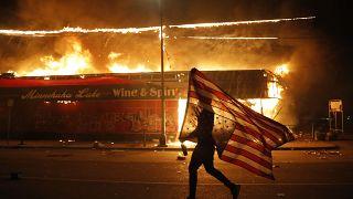 Un hombre con una bandera estadounidense frente a un comercio en llamas en Mineápolis
