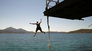 A boy dives into the sea from an old dock on the Aegean Sea island of Milos, Greece, Sunday, May 24, 2020.