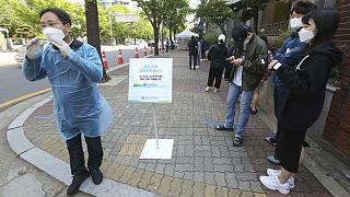 A medical staff, left, wearing a face mask shouts that the COVID-19 testing is over as people waiting for the test at a hospital in Seoul