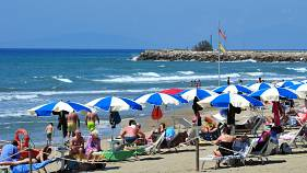 People enjoy a sunny day at an establishment on the beach in Tuscany's Castiglione della Pescaia, Italy, Sunday, May 24, 2020.