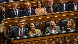 Spanish Prime Minister Pedro Sachez (L, bottom row) and Pablo Iglesias (second from the right, bottom row) in parliament.