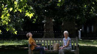 امراتان تجلسان على مقعد خشبي في إحدى حدائق لندن - 2020/05/26