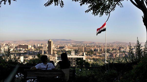 شاب ورفيقته يجلسان في حديقة عمومية مطلة على العاصمة السورية دمشق - 2019/07/24