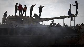 Libya'nın Bingazi kentinde tahrip edilen bir tankın üzerinde kutlama yapan halk (arşiv)