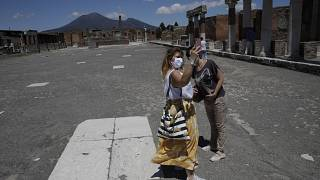 Two women take a selfie as they visit the archeological site of Pompeii, Italy, as the site reopened to the public after a two-month lockdown due to the COVID-19 pandemic