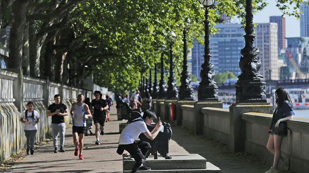 La gente disfruta del clima soleado y cálido a orillas del río Támesis en Londres, el jueves 28 de mayo de 2020, tras el alivio gradual del cierre de Covid-19.