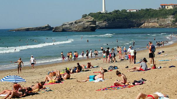 People sit on Biarritz beach, southwestern France, Saturday, May 30, 2020.