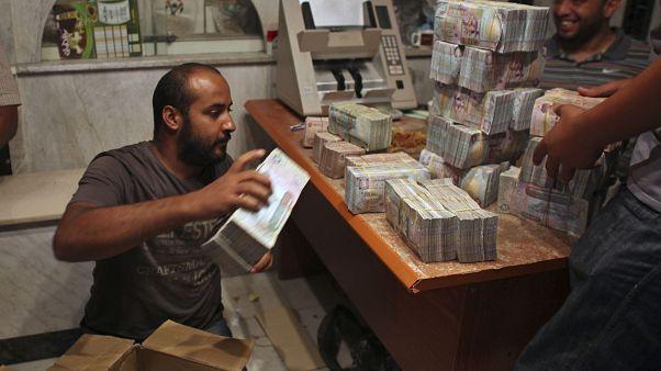 مواطن ليبي يعد رزم من الأموال في طرابلس