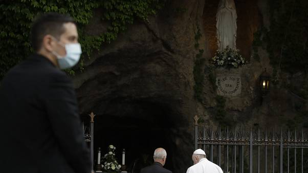 A priest wears face mask to prevent the spread of COVID-19, as Pope Francis prays during a rosary in Vatican gardens Saturday, May 30, 2020.