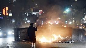 A man films himself in front of a fire in the middle of Melrose Avenue, Saturday, May 30, 2020, in Los Angeles.