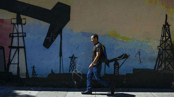 A man walks past a mural featuring oil pumps and wells in Caracas, Venezuela