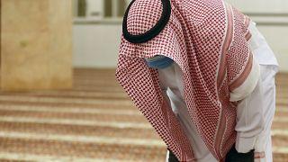 Suudi Arabistan'da eldiven ve maskesiyle camide namaz kılan bir kişi