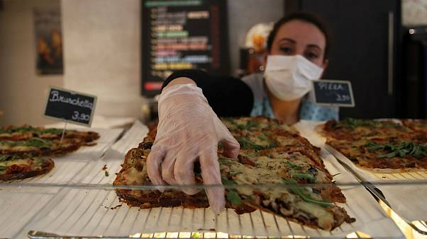 A baker woman wearing gloves and protective mask serves a bruschetta, in Paris
