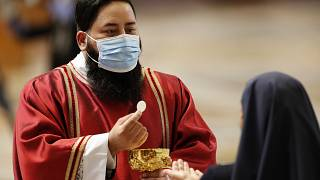 A deacon wearing a mask gives the communion to a nun during a Mass celebrated by Pope Francis in St. Peter's Basilica at the Vatican, Sunday, May 31, 2020