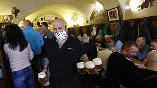 A waiter carries beer as a traditional beer pub opens in Prague, Czech Republic