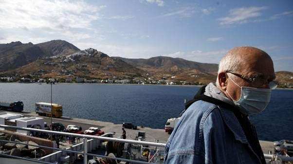 A passenger wearing a face mask to prevent the spread of the new coronavirus, stands on the deck of a ferry as it approaches the Aegean Sea island of Serifos