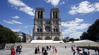 People walk on the forecourt of Notre Dame's Cathedral, in Paris, Sunday, May 31, 2020