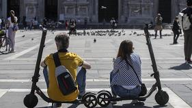 A woman and a man relax sitting on their scooters at the Duomo square, in Milan, Italy, Monday, May 25, 2020.