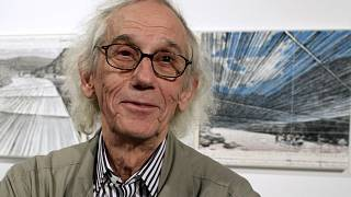"""This Jan. 23, 2013 photo shows artist Christo in front of his proposed """"Over the River"""" project at the Metropolitan State University Center for Visual Art in Denver, US."""