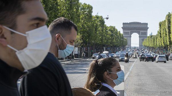 Des personnes portent des masques pour aider à freiner la propagation du coronavirus sur l'avenue des Champs-Élysées à Paris, le samedi 16 mai 2020.