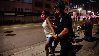 A police officer arrests a woman as protests over the death of George Floyd continue Sunday, May 31, 2020, in Los Angeles