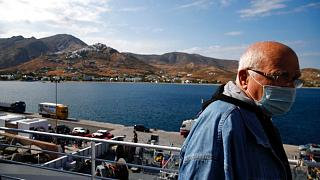A passenger on the deck of a ferry as it approaches the Aegean Sea island of Serifos, Greece, on Tuesday, May 26, 2020.