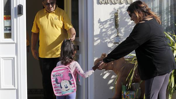 A mother drops off her daughter at the Little Darling home-based Childcare after nurseries and primary schools partly open in England